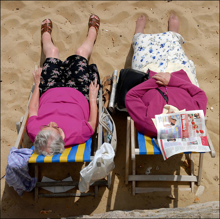Elderly ladies relax in the sun on Bournemouth beach.