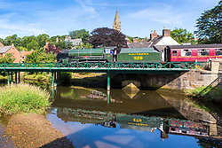 "© Licensed to London News Pictures. 18/07/2018. Ruswarp UK. 1934 Locomotive 926 ""Repton"" travels on the North Yorkshire Moors Railway across the river Esk in the picturesque village of Ruswarp, north Yorkshire this morning. Photo credit: Andrew McCaren/LNP"