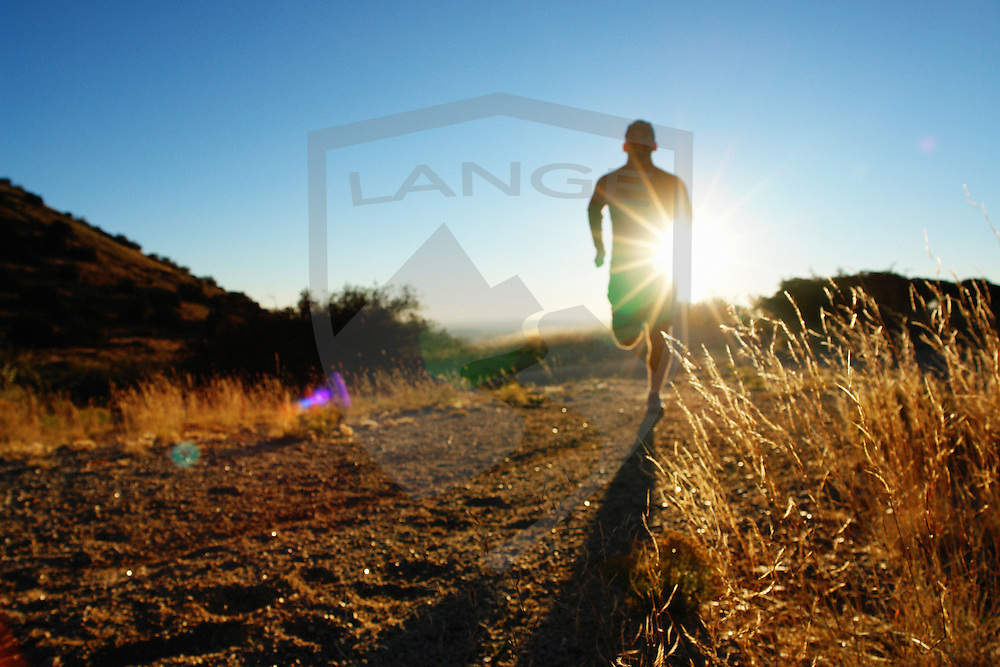 the sandia mountains of albuquerque new mexico offer myriad outdoor sports and recreation opportunities, including trail running in the foothills.  here, a trail runner man cross country runs with sun lens flare in the landscape, defocused