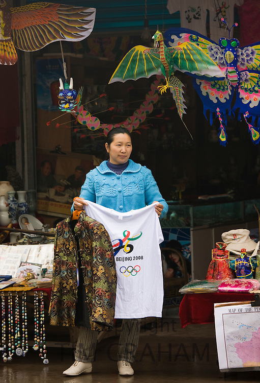 Souvenir seller sells Beijing Olympic Games 2008 t-shirts and jackets to passing tourists in Fengdu, China