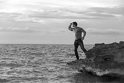 man standing on a rock formation in the ocean looking out