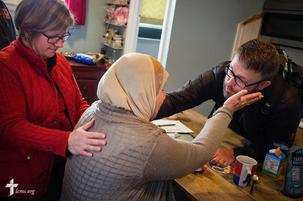 The Rev. Adam DeGroot, new national missionary and pastor at Shepherd of the City Lutheran Church, and Deaconess Pamela Nielsen of LCMS Communications, pray with a woman in his family's parsonage on Monday, Nov. 2, 2015, in Philadelphia. The woman was asking for information regarding her missing son.  LCMS Communications/Erik M. Lunsford