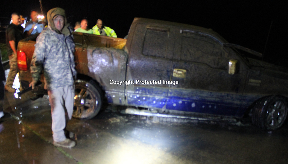 RAY VAN DUSEN/BUY AT PHOTOS.MONROECOUNTYJOURNAL.COM<br /> Sheriff Cecil Cantrell, left, requests help in breaking out the window of a stolen Ford F-150 recovered from the Tennessee-Tombigbee Waterway last week.