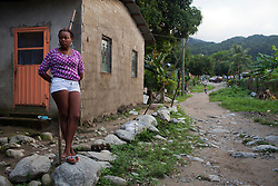 A woman stands on the side of the road on January 20, 2013  in Sambo Creek, Honduras. Sambo Creek is a Garifuna community on the Caribbean coast of Honduras that has a very high HIV incidence rate. (David Rochkind/ Pulitzer Center)