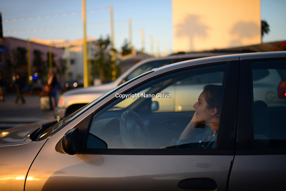 Young driver woman talking on mobile from inside car, Santa Monica, California.
