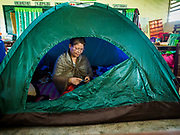 20 JANUARY 2018 - CAMALIG, ALBAY, PHILIPPINES: GEANNY NIPA mends clothes in a tent in a classroom at the Barangay Cabangan evacuee shelter in a school in Camalig. She set up the tent because the roof in the classroom leaks. There are about 650 people living at the shelter. They won't be allowed to move back to their homes until officials determine that Mayon volcano is safe and not likely to erupt. More than 30,000 people have been evacuated from communities on the near the Mayon volcano in Albay province in the Philippines. Most of the evacuees are staying at school in communities outside of the evacuation zone.   PHOTO BY JACK KURTZ