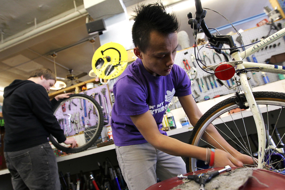 Youth Express apprentices Koua Yang, 15, right, and Marcus Wachholz, 17, refurbish donated bikes at Express Bike Shop in St. Paul, Minnesota, February 4, 2013.  By fixing and selling bicycles, youth apprentices learn mechanical, business, and entrepreneurial skills. All proceeds from bike sales go towards funding the program.