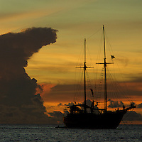Traditional Indonesian vessel at anchor of Pisang Islands with anvil shaped thunderhead cloud at sunset.<br /> Pisang Islands, W of Fak Fak Peninsula, Ceram Sea.<br /> Alfred Russel Wallace sailed through this very area in traditional boats.