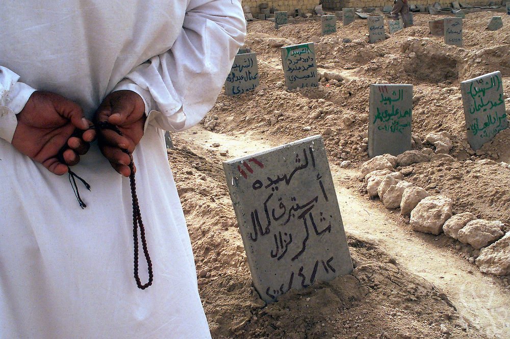 An Iraqi man hold prayer beads as he mourns May 03, 2004 over graves in a soccer field converted to a cemetary in the flashpoint Iraqi city of Fallujah.  Residents began to bury their dead in the soccer field after the regular city cemetary overflowed during a month long seige of the city by U.S. Marines that killed an estimated 1300 Iraqis.