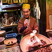 A vendor sells roasted nuts at Nishiki Market in Kyoto, Japan.
