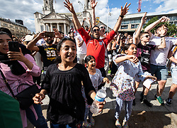 © Licensed to London News Pictures . 07/07/2018. Leeds, UK. Football fans celebrate England's victory over Sweden in the World Cup in Leeds City Centre after watching the match on a big screen in Millennium Square . Photo credit: Joel Goodman/LNP