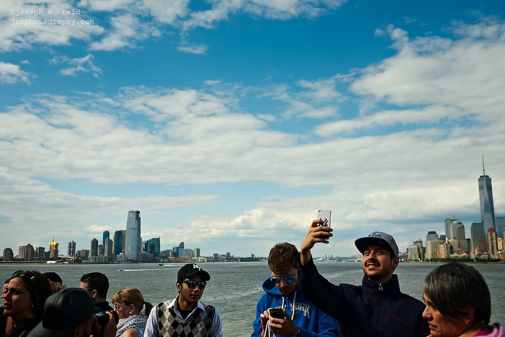 Young man taking self-portrait with iPhone on Staten Island Ferry, New York, NY, US