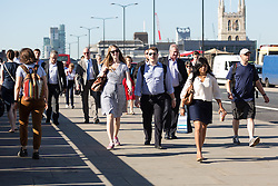 © Licensed to London News Pictures. 19/07/2016. LONDON, UK.  Commuters walk to work over London Bridge during hot weather in London this morning. Today is forecast to be the hottest day of the year so far.  Photo credit: Vickie Flores/LNP