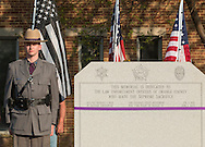 Goshen, New York - A New York State trooper stands at attention by the monument during the Orange County Law Enforcement Officer Memorial Service at the entrance of the Orange County Courthouse on May 8, 2015. The memorial service honors the memory of the members of the Orange County law enforcement community that died in the line of duty. The service also pays tribute the families and loved ones left behind for their courage, dignity and perseverance.