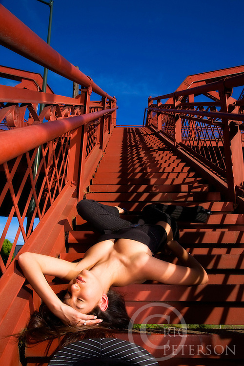 young asian woman laying upside down on stairs pretending to have fallen