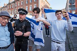 © Licensed to London News Pictures. 15/05/2018. Bristol, UK. A group of young men with an Israeli flag confront a protest and march in solidarity with Palestine after 70 Years since the Nakba (Catastrophe) and with the Great March of Return in Palestine, calling for justice, equality and the implementation of the right of return of Palestinians to their homes in what is now Israel. Protests are being held in other cities following 58 Palestinian protesters having been killed and 2,000+ injured yesterday by Israeli forces firing on the 35,000-strong protests at the Gaza border, the most lethal in a string of such episodes as Palestinians have protested for the right to return to occupied lands over the past 6 weeks. The Bristol protest was organised by Bristol Palestine Solidarity Campaign and Bristol Stop the War Coalition with other groups. The campaign says that Between 1947 and 1949, Zionist paramilitary forces ethnically cleansed and eradicated over 500 villages and cities in Palestine, displacing 750,000 Palestinians and taking over 78% of the land. Palestinians call this process the 'Nakba', or catastrophe. Today, over 7 million Palestinian refugees are scattered around the world, many of whom live in refugee camps in the West Bank, Gaza, Lebanon, Jordan, and Syria. Photo credit: Simon Chapman/LNP