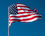 Alaska.  Large red, white, and blue American flag waving in a strong breeze against a blue sky background in Anchorage in April.