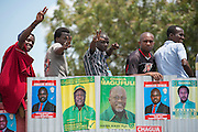 Dar es Salaam, Tanzania - 10/1/15 - Opposition supporters sit on a wall plastered with posters for various politicians at a rally in Temeke municipality in Dar es Salaam, Tanzania on October 1. Tanzania heads to the polls on October 25. Photo by Daniel Hayduk