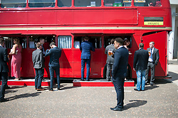 TODAY PICTURE © Licensed to London News Pictures. 06/06/2014. Epsom, UK. People at a bar converted from a red bus.  Ladies Day today 6th June 2014 at Epsom 2014 Investic Derby Festival in Surrey. Traditionally, elegant, fashionable racegoers gather for a classic day's racing at Epsom Racecourse, Surrey. Photo credit : Stephen Simpson/LNP