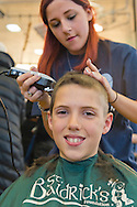 JOSEPH ROSENTHAL, 11, of Merrick, has his head shaved by KELSEY BAZAREWSAKI, a junior who takes cosmetology at Calhoun High School, at St. Baldrick's fund raising event at Calhoun. The Long Island school exceeded its goal of raising $50,000 for childhood cancer research. Plus, many ponytails cut off will be donated to Locks of Love foundation, which collects hair donations to make wigs for children who lost their hair due to medical reasons.