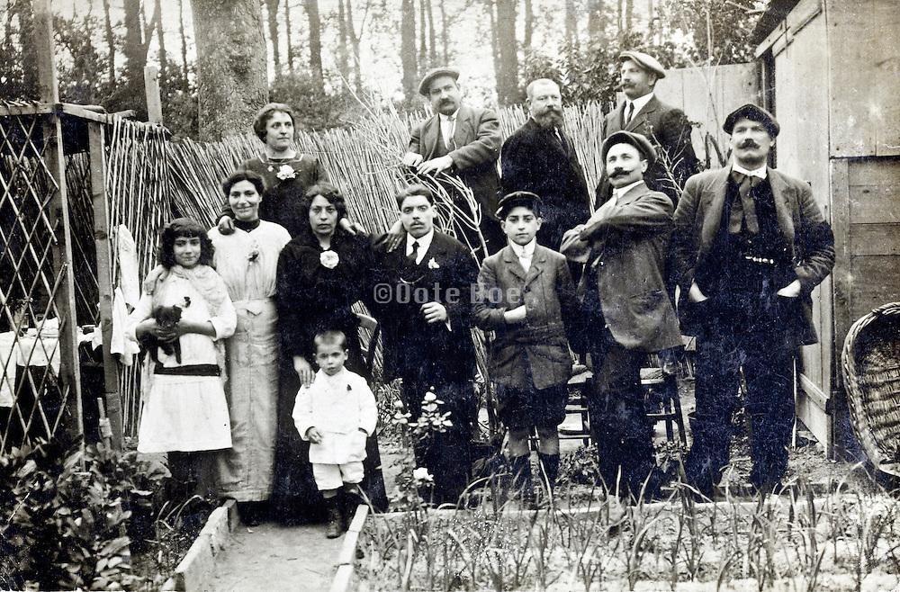 family group portrait in outdoors setting with vegitable garden