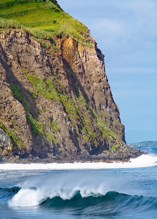A wave breaks under a grassy cliff outside the the town of Horta on the island  of Faial in the Azores. The Azores consist of nine Portuguese islands in the North Atlantic Ocean. Historically they were involved with whaling but now earn most of their income from agriculture and tourism. The Islands mark the most westerly point of the E.U.