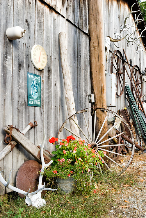 Rustic decorations outside a weathered barn with elk antlers, an old wagon wheel, and other things pack-ratted and collected from yeas of life around an old Pennsylvania farm.