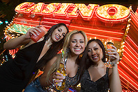 Portrait of three young women toasting in front of illuminated casino, Las Vegas, Nevada, USA