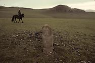 Mongolia. horse riders in front of  a stone statue (Turkish 6th century)                      / Cavaliers passant devant un alignement de statues monolithes anthropomorphes. (Granit, VI-VIIIème siècle). / Ces statues représentent des  - 'idoles de pierre -  (KUN TCHULUU), typiques de l'art monumental des steppes d'Asie Centrale. D'après la coutume du culte des Ancêtres, ce genre de statue était érigée à la surface d'une tombe d'un noble guerrier, à l'époque des Turcs Célestes. Leur visage présente pratiquement toujours les mêmes caractéristiques : faciès plat, pommettes saillantes, yeux en amandes et moustache. L'idole, vêtue d'une robe avec ceinture, a le bras droit plié au niveau du coude et tient une coupe. (Sum de DJARGALAN, dans l'aymag de GOV ALTAY  / /11    L0006224  /  P0002616