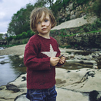 Close up of young child wearing red jumper standing by river