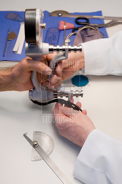 close up of a doctor's hands administeering a strength test of a patient's grip