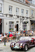Classic Morgan drop head sports car being driven past diners al fresco at restaurant in Kerk Straat, Damme, Belgium