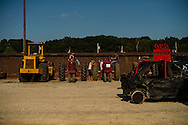Volunteers lounge on and around their tractors used for 'picking' vehicles unable to exit the demolition derby track under their own power at Summitt County Fairgrounds, Thursday, July 26, 2016 in Tallmadge, Ohio.