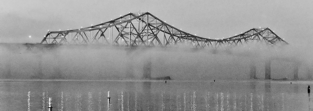 An early morning fog partially obscures the Tappan Zee Bridge.  Shot from the east side in Tarrytown, NY