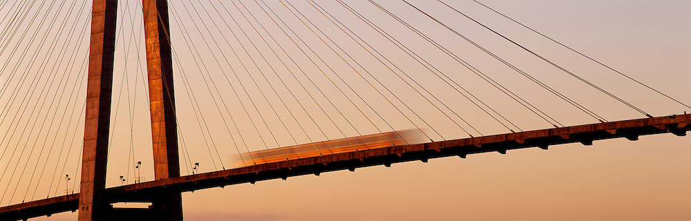 Skytrain blurs by on Skytrain bridge at sunrise, crossing Fraser River