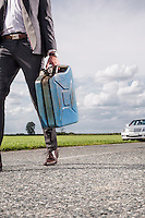 Low section of young businessman carrying gasoline can with broken car in background at countryside