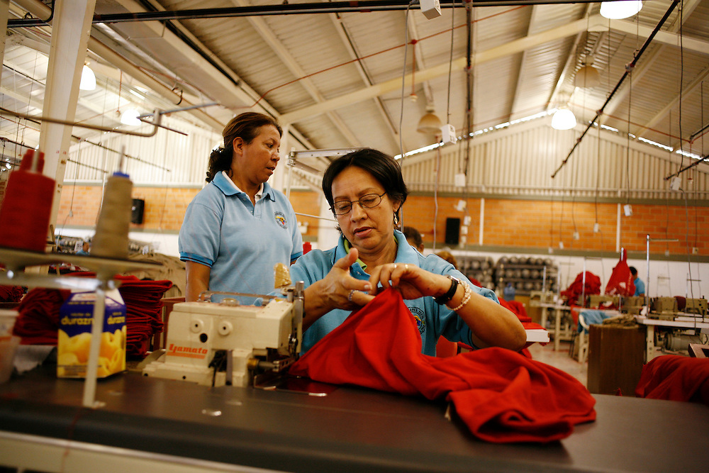 "Workers make red t-shirts for the government in a factory located in a compound referred to as an ""endogenous zone"" located in Catia barrio (one of the largest barrios in Caracas). The compound is part of the government's plan to build zones for work, entertainment, health care, recreation and other activities and services for nearby residents."