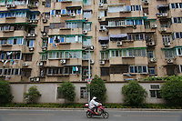 A woman on an electric bike riding by an apartment building in Hangzhou, China.