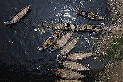 April 17, 2018 - Dhaka, Bangladesh - Bangladeshi commuters use boats to cross the Buriganga River. The chemical waste of mills and factories, household waste eventually makes its way into the Buriganga River, which is considered to be Dhaka's lifeline. Thousands of people depend on the river daily for bathing, washing clothes, irrigation of food and transportation of goods. The river has suffered extreme biodiversity loss and has now turned black. A large swathe of the Buriganga River, which is the lifeline of the capital, has turned pitch-black with toxic waste, oil and chemicals flowing into it from industrial units. (Credit Image: © Zakir Hossain Chowdhury via ZUMA Wire)