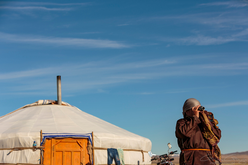 Dolgormaa, a Mongolian nomad, scans the distant horizon with a monocular, looking for members of her family returning to the camp.