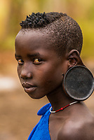 Teenaged girl with ear modification to hold a clay disc, Mursi tribe, Mago National Park, Omo Valley, Ethiopia.