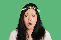 Portrait of a surprised young woman over green background