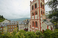 View of St Peter Church and colorful Bacharach housing, with a cloudy sky and mountains in the background, Bacharach, Germany.