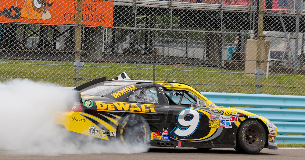 WATKINS GLEN, NY - AUG 12, 2012:  Marcos Ambrose (9) holds off a hard charging field to win the Finger Lakes 355 at The Glen in Watkins Glen International, NY.
