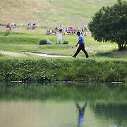 K.J. Choi, SOuth Korea, heads to the 16th green while reflected in a pond during the final round of the Travelers Championship at the TPC River Highlands, Cromwell, Connecticut, USA. 22nd June 2014. Photo Tim Clayton