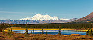 Scenic view of Denali (formerly Mt. McKinley) and pond at Broad Pass along Parks Highway in Interior Alaska. Autumn. Morning.