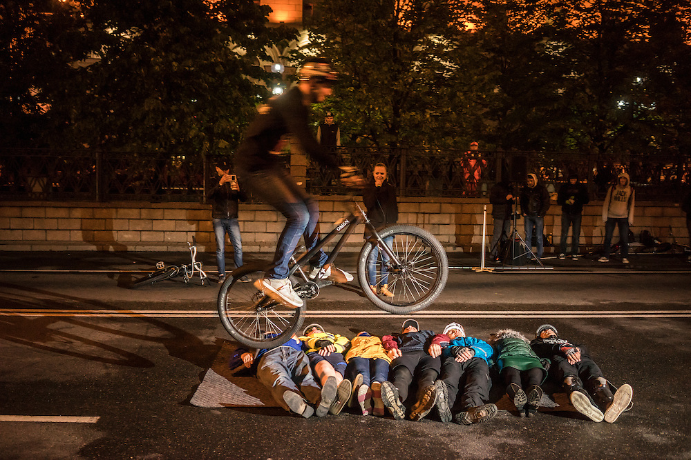 A cyclist performs a stunt jumping over volunteers on the ground during a cycling festival on Thursday, September 22, 2016 in Minsk, Belarus.