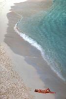 Virgin Islands National Park, St. John, US Virgin Islands --- A woman lies on a pristine beach on St. John, U.S. Virgin Islands. --- Image by © Owen Franken