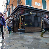 People walks in Central Venice in front of a Cartier Shop during seasonal High Tide. A few days of exceptional high tides up to 120cm are expected during the next few days