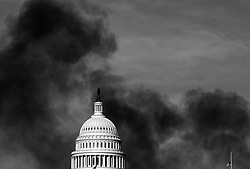 Thick black smoke from a large fire on Pennsylvania Avenue surrounds the US Capitol Building.